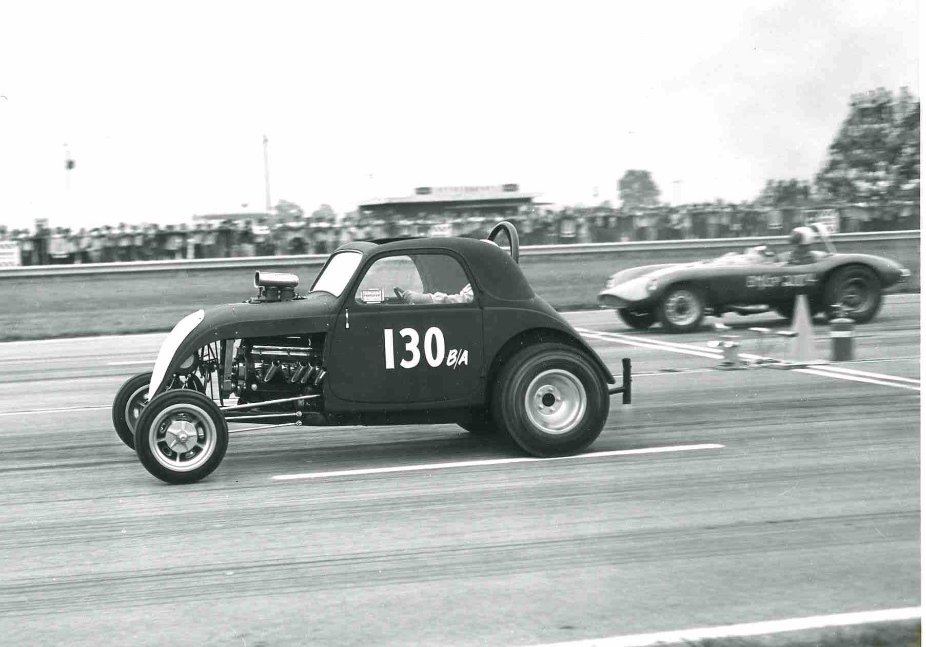 Built by Shreve Automotive, Shreveport, LA, the Topolino in this configuration, which included a Ronnie Scrima chassis powered by a supercharged Olds with B&M Hydrostick, first raced at Indy 1962, where it broke an axle in the semis finals. Famed camshaft manufacturer Joe Lunati is pictured in his sports car in the far lane.